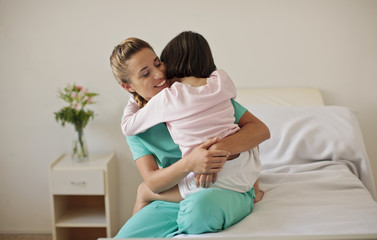 Young girl hugging nurse in hospital room.