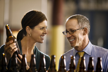 Two smiling colleagues examining a row of beer bottles.