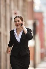 Businesswoman walks outdoors talking an a cellphone.