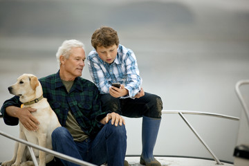 Man and his grandson sitting on the deck of a boat and looking at something on a cellphone.