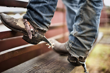 Person standing against iron gate wearing dirty worn-in jeans and cowboy boots.