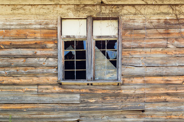Old broken windows with shattered glass in a rustic wooden building.