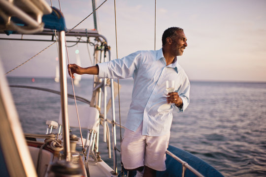 Mature man looking at view from boat as he has a glass of wine.