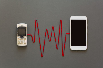 Old phone and new smartphone connected by red pulse laying on grey paper background. Scissors cut the thread. Break up. Upgrade phone technology or generation connection concept. Flat lay. Top view