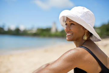 Smiling woman sitting on beach, looking out at water.