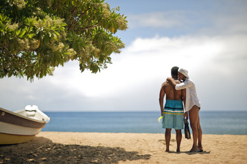 Mature woman hugging her husband at the beach.