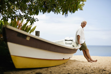 Mature man leaning on the dinghy at the beach.