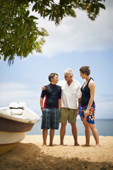 Boy standing next to dinghy at the beach with his parents.