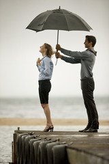 Mid-adult businessman shielding his business partner with umbrella.