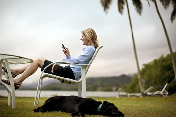 Mid-adult businesswoman text messaging while sitting by the sea.