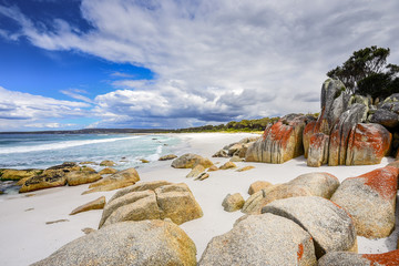 Bay Of Fires, Cosy Corner, Tasmania, Australia: Gorgeous sunny summer coast view to blue Tasman Sea with crystal clear water surrounded by red orange colorful shore rocks and white sandy beach