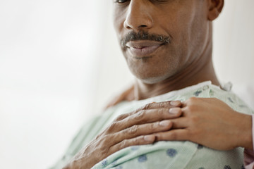 Hospital patient touches the comforting hand laid on his shoulder.