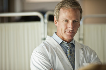 Handsome doctor with a good bedside manner listening to his patient.