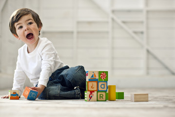 Toddler boy playing with blocks on the floor.