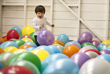 Little boy excitedly running in a room full of balloons.