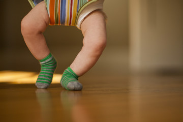 Legs of a baby on a hardwood floor while bouncing in a baby jumper.