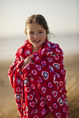 Portrait of a smiling young girl wrapped in a heart printed towel at the beach.