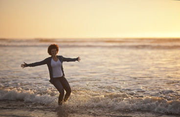 Portrait of a laughing mid adult woman standing ankle deep in the sea at the beach.