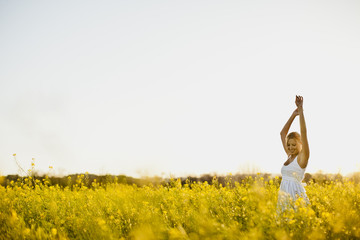 Portrait of woman in a white dress standing in a meadow.