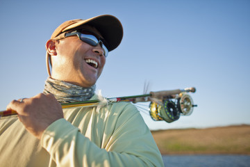 Smiling mid adult man carrying a fishing rod over his shoulder while at a lake in the sunshine.