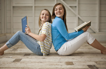 Two smiling teenage girls sitting back to back while reading books on the floor of a garage.