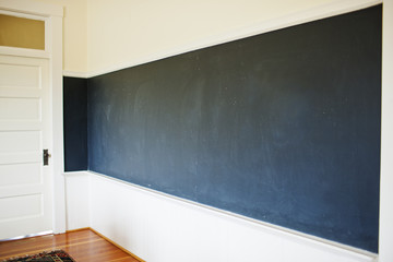 Empty chalkboard covering the wall of a classroom.