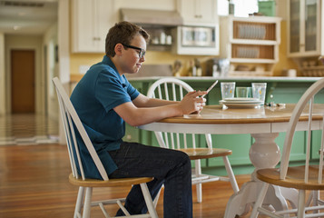 Teenage boy sitting at a kitchen table and looking at a digital tablet.