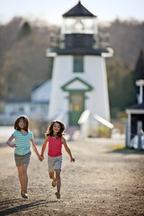 Young sisters running in front of lighthouse.