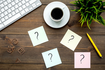 Question mark on sticky notes on office desk on dark wooden background top view. FAQ concept. Working with clients. Troubles in work.