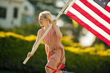 Smiling young girl carrying an American flag while running through her back yard.