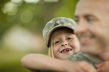 Smiling male soldier piggy-backing his young daughter.