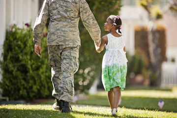 Young girl walking hand in hand with her father in their back yard.