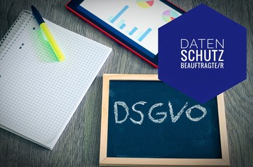 Plate with the inscription DSGVO (Datenschutzgrundverordnung) in English GDPR with a tablet and block and datenschutzbeauftragter in english data protection officer