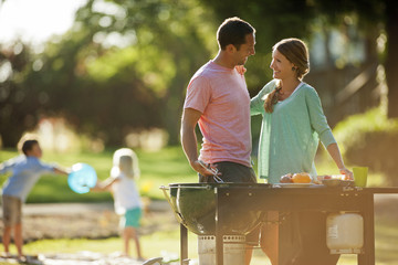 Smiling couple standing by a barbecue in their back yard.