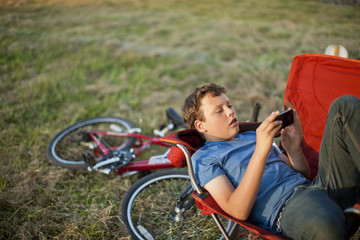 Teenage boy lying in a field looking at a smart phone.