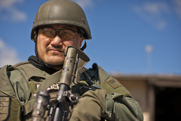 Mid adult military policeman holding a gun.