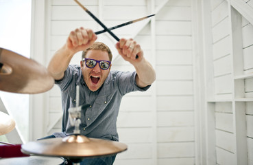Excited mid adult man gesturing with drumsticks while sitting at a drum kit inside a garage.