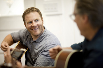 Smiling mid adult man playing acoustic guitar with a friend.