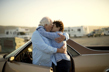 Mature couple embracing by a car.
