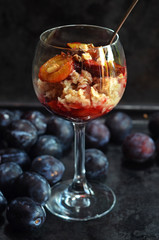 Healthy oatmeal with plums in a glass
