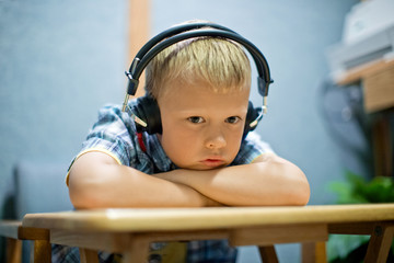 Daydreaming young boy wearing headphones while listening to music at a desk.