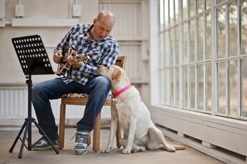 Mid-adult man playing a guitar and singing to his dog while sitting in a chair.