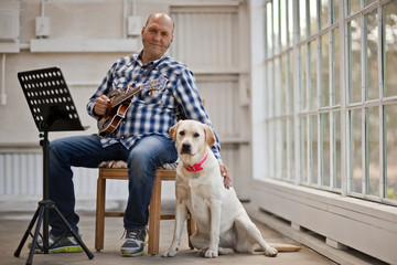 Portrait of a mid-adult man holding a guitar and petting his dog while sitting in a chair.