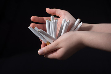 Hand is giving out bundle of cigarettes on black
