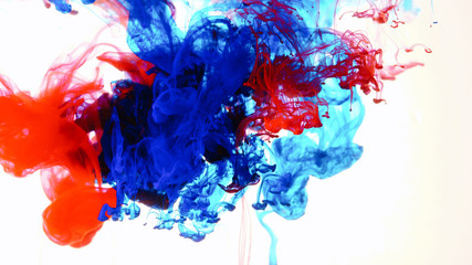 Red and blue ink in water shooting with high speed camera. Indigo paint dropped, reacting, creating abstract cloud formations metamorphosis on white. Art backgrounds