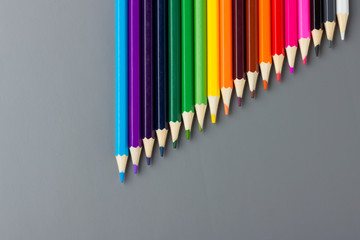 Color pencils on a gray background are descending in length.