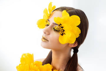 Beauty portrait of a brunette with extended eyelashes in the image of a tulip. On a white background