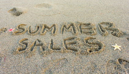 the word summer sales / the word summer sales written on the sand