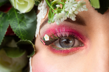 Portrait of a beautiful brunette with huge erect eyelashes in the image of spring with a wreath of roses on his head on a white background.