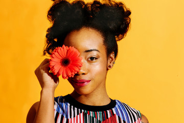 Portrait of a young woman with curly hair covering her eye with a flower, isolated on yellow studio background